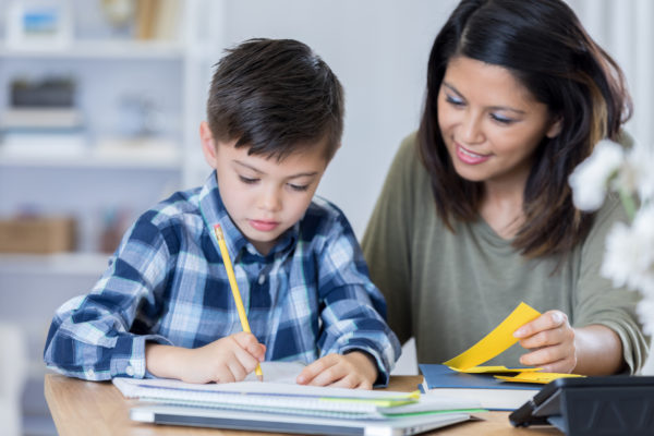 adult helps elementary age kid with homework